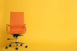 Modern office chair on yellow background. Space for text