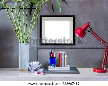Modern office desk with laptop, flowers vase and blank  picture frame