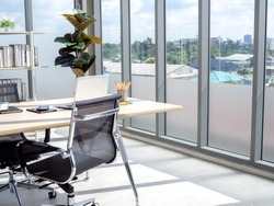 Modern office interior with huge windows with blue sky view. Wooden desk in corner of contemporary workplace. Two empty chairs with laptop computer in CEO room for the new employee's job interview.