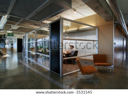 Modern office interior with separate (semi-private) meeting room with glass walls