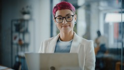 Modern Office: Portrait of Beautiful Authentic Specialist with Short Pink Hair Standing, Holding Laptop Computer, Looking at Camera, Smiling Charmingly. Working on Design, Data Analysis, Plan Strategy