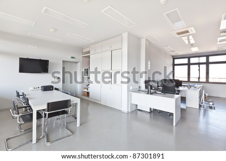 Modern office with white furniture, cupboard, conference desk and walls and with plasma TV on the wall