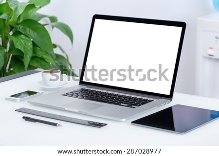 Modern office workspace with laptop computer, tablet pc and smartphone on the desk. There is a laptop, tablet computer, smartphone, cup of coffee on the table. For design presentation or portfolio.