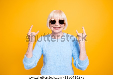 Modern old lady hold hands up and showing sign rock and roll isolated on vivid yellow background