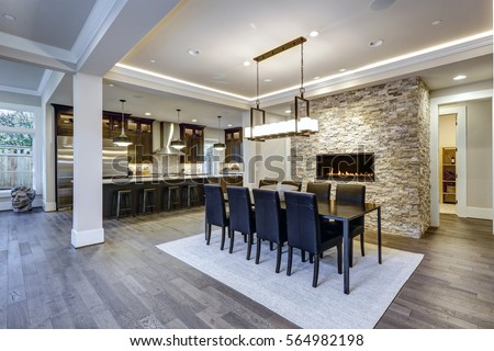 Photo of Modern open floor plan dining room design accented with stone fireplace wall facing black dining table lined with leather chairs and illuminated by rectangular chandelier. Northwest, USA