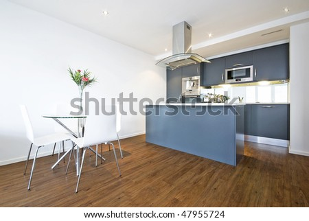 Modern open plan living area with dining table and fully fitted kitchen