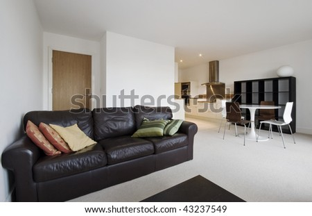 modern open plan living room with kitchen view in the background #43237549