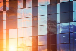 Modern or futuristic architecture reflection in glass with sunset. Abstract construction industry