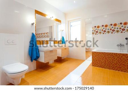 Modern Orange Bathroom With Two Sinks And Big Mirror
