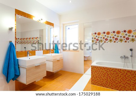 Modern orange bathroom with two sinks for big family
