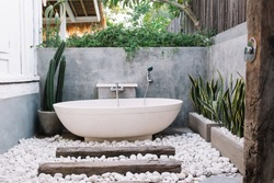 Modern outdoor bathroom with oval white ceramic bathtub decorated with green exotic plants and pebbles on terrace of luxury villa in Bali