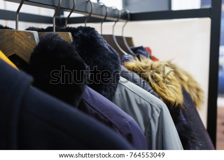 Modern outerwear in a shop on a hanger. Jackets, parks and warm outerwear of different colors and denim for youth. Outerwear of different styles on the hanger in the showroom. Soft focus. - Shutterstock ID 764553049