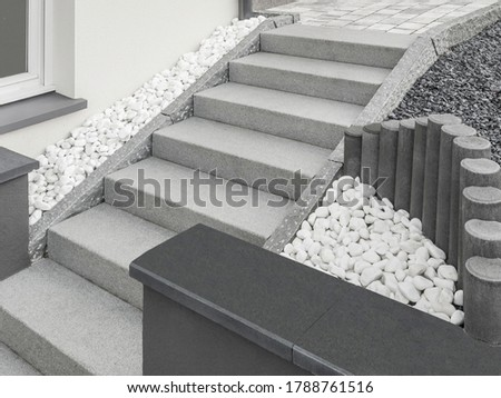 Modern outside staircase made of granite with large pebble drainage and stelae Foto d'archivio ©