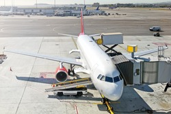 Modern passenger airplane parked to terminal building gate at airside apron of airport with airplane parts jet engine wing windows gear noon sun view air travel panoramic aerial background