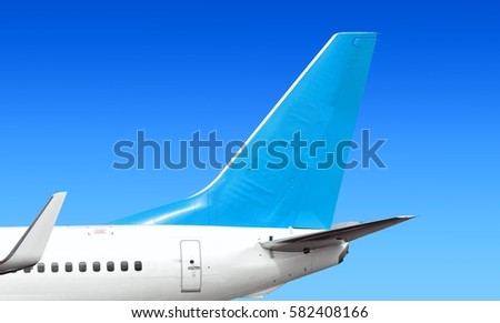Modern passenger jet aircraft side tail silhouette aircraft parts wing passenger window aft exit fin antenna jet engine exhaust design air travel isolated on blue sky light blue panoramic background #582408166