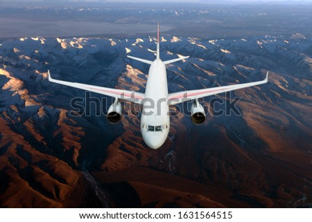 Modern passenger wide-body plane in flight. Aircraft flies over over brown mountains. Aerial view.