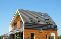 Modern Passive House Exterior. Modern energy efficiency house with skylight windows and solar panels on the roof top.