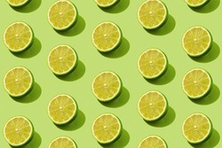 Modern pattern with lime slices on a green background illuminated by bright summer sunlight - Pop art design minimal creative concept - Flat lay composition