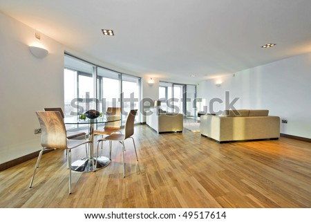 Modern penthouse living room with large designer sofas and dining table and chairs