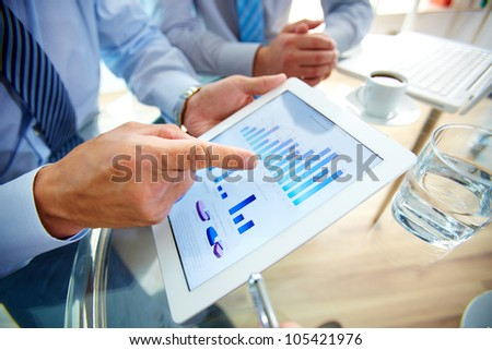 Modern people doing business, graphs and charts being demonstrated on the screen of a touch-pad