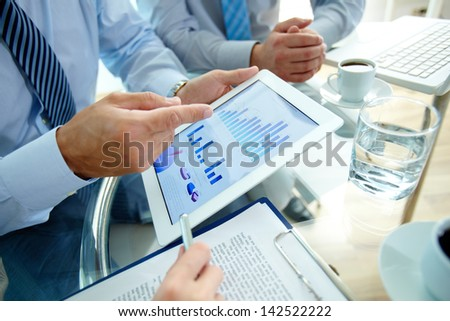 Modern people doing business, graphs and charts being demonstrated on the screen of a touchpad