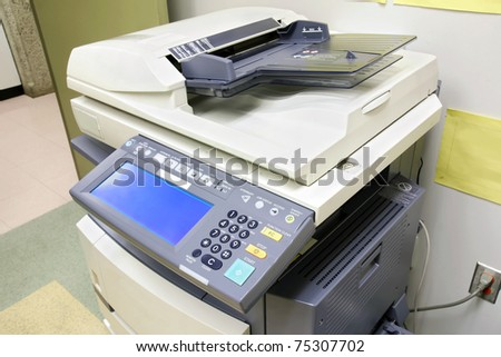 Modern photocopier with digital display plugged to the wall in the office supply room.