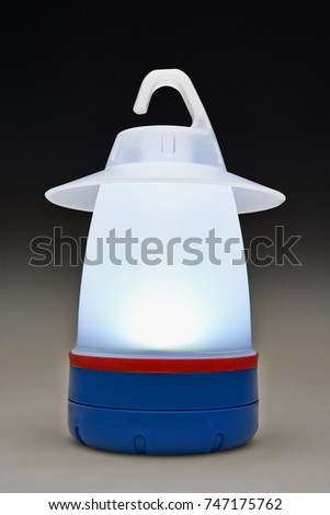 Modern plastic camping light on table illuminated and isolated #747175762