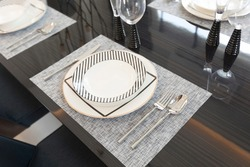 modern plate setting on dinning table with decorative candle stand in modern home.