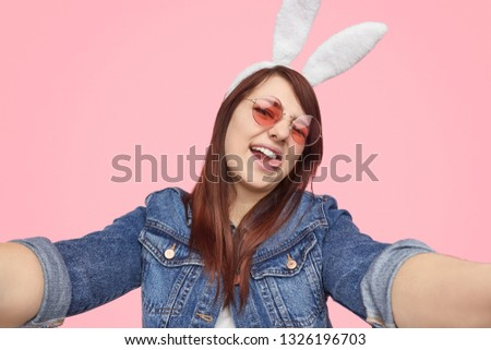 Modern plump woman in denim jacket and white ears showing tongue while taking selfie on pink background