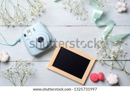 Modern polaroid camera, macaroon cookies, photo frame, flowers on rustic blue wooden background. Top view, tender minimal flat lay style composition. Womens desk, fashion blogger, beauty technology