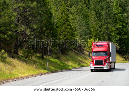 Modern popular for professional drivers model of semi truck in red going with dry van trailer transporting commercial cargo to destination warehouse by wide highway with green forest on background
