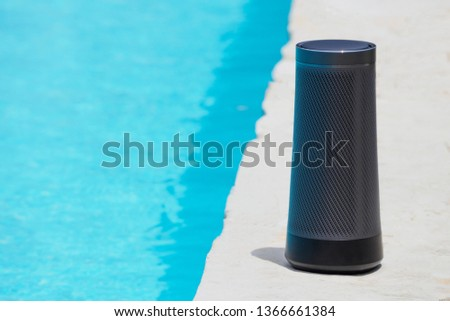 Modern portable music speaker with voice assistant near the swimming pool. #1366661384