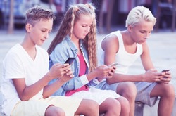 Modern positive kids spending time together outdoors using mobile gadgets