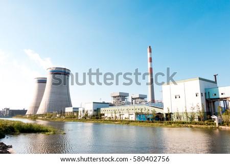 modern power plant near river in blue sky #580402756