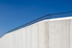 Modern prison wall against blue sky.
