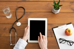 Modern private practice of doctor and patient visit. Hands of female therapist in white coat works on tablet with blank screen on wooden table with stethoscope, apple, plant and glasses, top view, pov