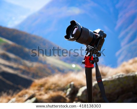 Modern professional camera on a tripod, outdoor photography in wildlife. Mountains background.