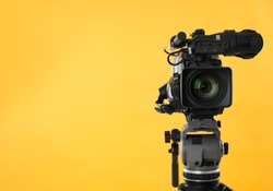 Modern professional video camera on yellow background. Space for text