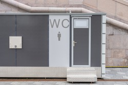 modern public toilet exterior outdoor. Modern Toilet metal building, outdoor, day time. Front view of modern restroom. Facade of outdoor lavatory with men women WC sign