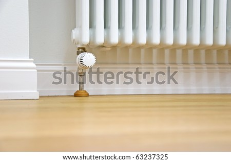 modern radiator at the wall and parquet floor