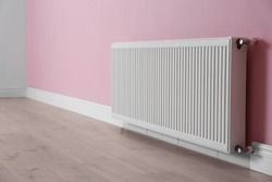 Modern radiator on color wall indoors. Central heating system