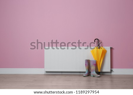 Modern radiator, rubber boots and umbrella near color wall with space for text. Central heating system