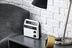 Modern radio receiver on table in room