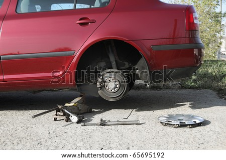Modern red car in changing wheel process. - stock photo