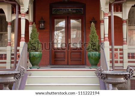 Modern red house and porch. Green shrubs in green vases outside.
