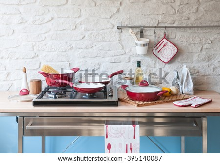 modern red kitchen behind brick wall with red cookware set