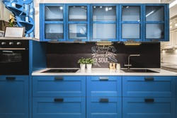 Modern red kitchen interior with black brick walls, wooden countertops with a built in sink and a cooker.  color of the year 2020 pantone classic blue