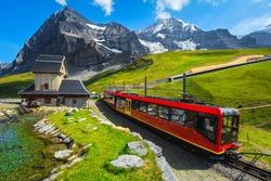 Modern red passenger train near the small mountain chapel. Cogwheel red tourist train coming down from the mountain station, Jungfraujoch, Bernese Oberland, Switzerland, Europe