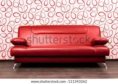 Modern red sofa in front of the wall with abstract wallpapers