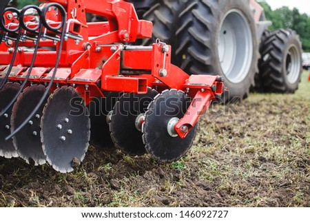 modern red tractor in the agricultural field; mechanism.